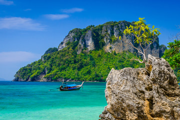 Tropical see with clear turquoise water, rocks, long tail boat and island. Typical thai landscape from Poda Island, West Railay Beach, Krabi, Thailand.