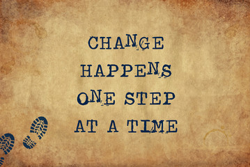Inspiring motivation quote of change happens one step at a time with typewriter text. Distressed Old Paper with Typing image.