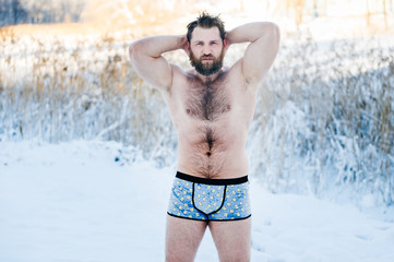 Portrait of russian bearded bodybuilder man with hairy body standing without clothes outdoors in winter on snow in cold weather after swimming and posing for camera. Healthy life concept.