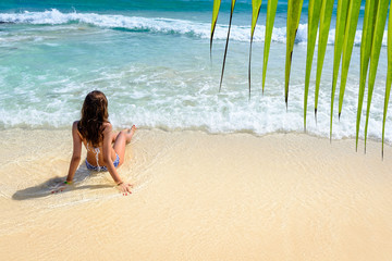 Attractive young caucasian woman in blue swimsuit sitting on a tropical beach and looking on sea. Photo from Playa Del Carmen, Riviera Maya, Mexico.