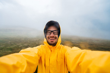Selfie portrait of a smiling and laughing traveller man in yellow raincoat and glasses in the clouds mountains in stromy weather with rain