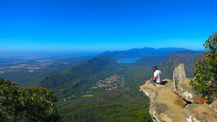Adventurous young man sitting on a height cliff edge at the top of the Boroka Lookout at the The Grampians National Park (Gariwerd), Victoria, Australia