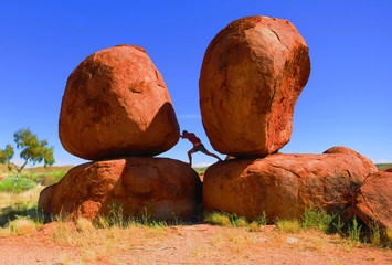 Bearded man attempting to push over a huge boulder rock in the the 'Devils Marbles' - an interesting natural rock formation in the outback of Australia, Northern Territory