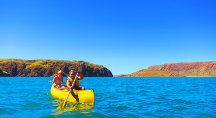 Two happy smile girls / women enjoying kayaking on the large freshwater Lake Argyle in Western Australia on a beautiful sunny day with clear blue skies and red rock mountains in the background
