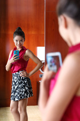 Woman taking smartphone selfie in the mirror of outfit in changing room at upscale store or at home trying on clothing. Weight loss, body image, self-esteem, shopping, fashion concept.