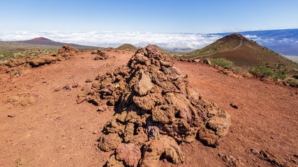 Pile of red lava rocks on Mauna Kea, Mauna Loa visible in the background.