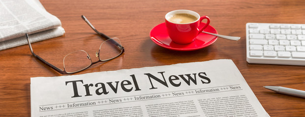 A newspaper on a wooden desk - Travel News