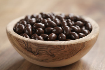 small chocolate dragee in wood bowl on table, coffee beans or pine seeds