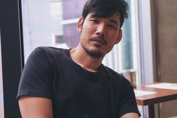 Portrait image of a young Asian man sitting in cafe with smiley face and feeling good