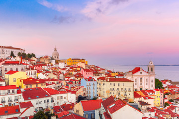 View of Alfama, the oldest district of the Old Town, Church of Saint Stephen and National Pantheon from belvedere Miradouro das Portas do Sol at scenic sunset, Lisbon, Portugal