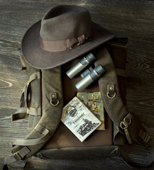Hat, Binoculars, passport, backpack, notepad lie together for travel on wood floor