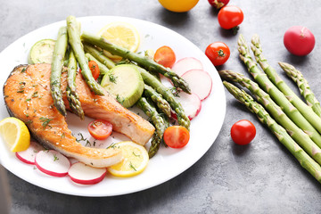 Steak of salmon with asparagus and vegetables on grey wooden table