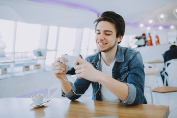 Attractive young man or freelance is sitting in cafe and using his mobile