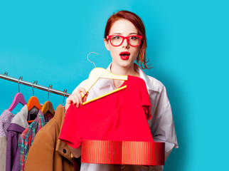 photo of beautiful young woman with shirt on hanger under heart shaped box near clothes on the wonderful blue background