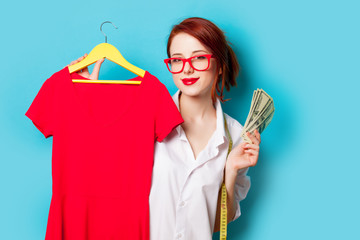 photo of beautiful young woman holding shirt on hanger on the wonderful blue studio background