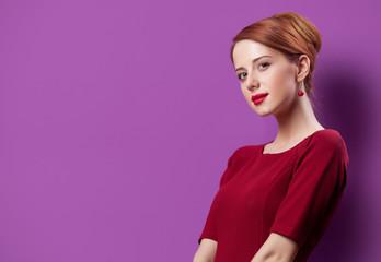 photo of beautiful young woman standing on the wonderful purple studio background