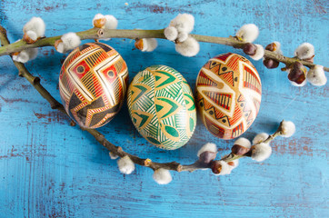 Easter colorful eggs and willow branches on blue wooden background. Springtime. Holiday card. Spring willow twigs with catkins and ornate eggs. Happy Easter.Still life with Pysanka. Easter background