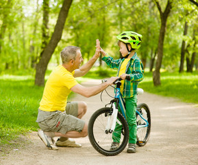 Grandfather and grandson give high five while cycling in the park