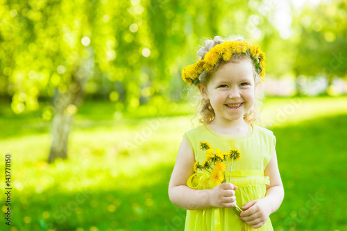 Happy girl with dandelions in summer park