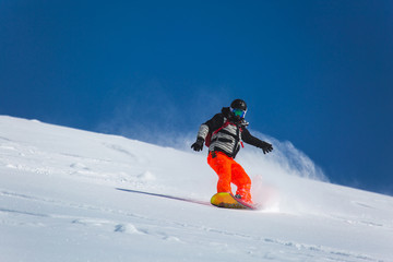 snowboarder snowboarding on fresh white snow with ski slope on Sunny winter day