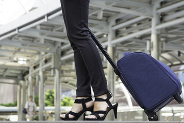 Woman traveler with bag, luggage, suitcase arrival at the airport during traveling. woman weighs travelling suitcase at the station or in the airport terminal. Travel and Trip for woman concept.