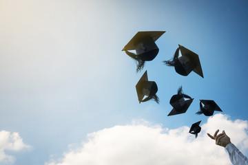 Graduates hands throwing graduation hats.