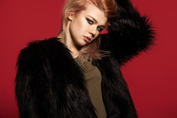 Stylish fashionable girl in a black fur coat faux fur on a red background