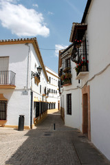 Spain. Andalucia. Ronda. Street of town with white houses, vertical view.