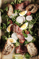 fresh salad with ham and boiled eggs on a rustic pan top view. Healthy lifestyle concept.