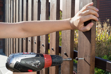 Close up of hand screewing wood plank to metal construction. Building a wooden fence with a drill and screw.