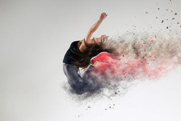Woman in jump in studio and disintegration effect
