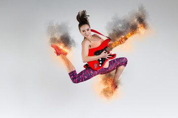 Woman in jump with a burning guitar in the studio