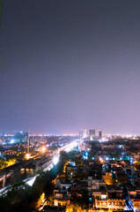 Noida cityscape at night with houses, office, skyscrapers, streets and metro rails visible. Lots of construction is visible as well showing the development