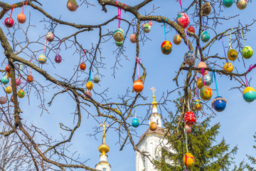 Easter eggs on a tree branch near the Church
