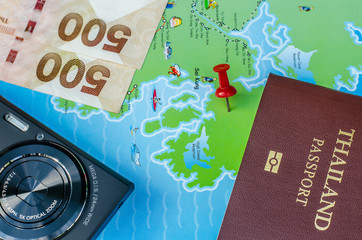 Black compact camera and map and money and passport on wood table