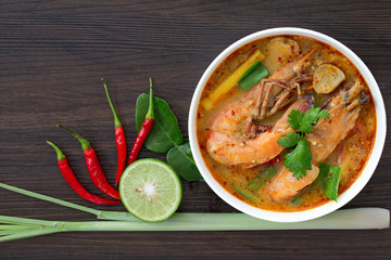 Tom yum kung in white bowl on wooden table, Still life image and Select focus, space for text.
