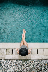 Young woman in hat relaxing near swimming pool. Top view