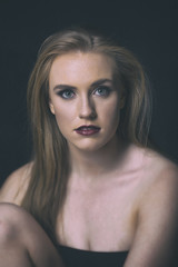 red head model with an edgy personality looking sexy in a dark studio with edgy lighting