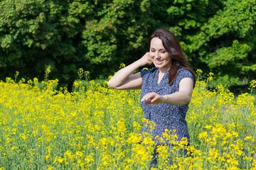 Beautiful woman in a yellow flowers field. Peoples