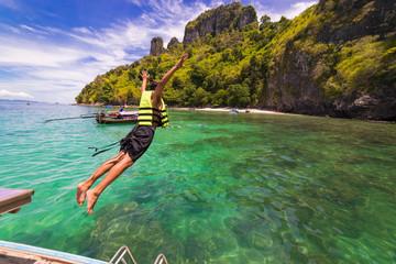 Young man jumping into the sea at koh chicken islands andaman sea Krabi ,South of Thailand