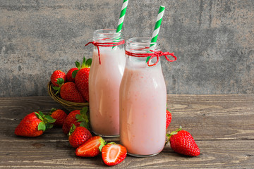 fresh strawberry smoothie in bottles with straw