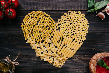 Dried pasta in heart shape top view. Pasta and vegetables on the dark wooden table