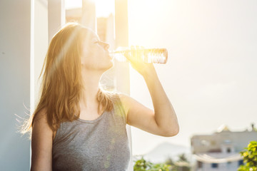 Young woman is drinking water on the sunset background