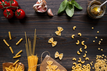 Dried mixed pasta and vegetables on the dark wooden table top view