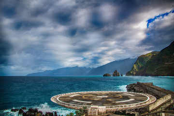 Helipad located in Porto Moniz, North of Madeira Island. In the background there are blue ocean waves, black rocks and green hills of the coastal line.