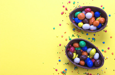 Easter chocolate egg with colorful explosion of candies and sweets on yellow colored background.
