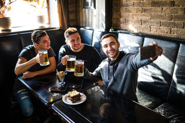 Handsome friends are drinking beer, doing selfie and smiling while resting in pub. Beer time.