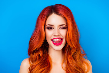 close up portrait of  funny attractive pretty girl with long ginger fair hair put out her tongue while standing on blue background