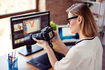 Side view  of female freelancer photographer cheking  photos on a digital camera while sitting at the table in workstation