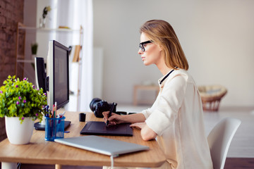 Side view  of female graphic designer working with interactive pen display, digital drawing tablet and pen on a computer in workstation